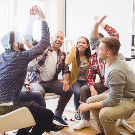 En arbetsgrupp som ger varandra high fives och arbetar som ett team. Det kan du också lära dig med coachning och mental träning för ledare och medarbetare.