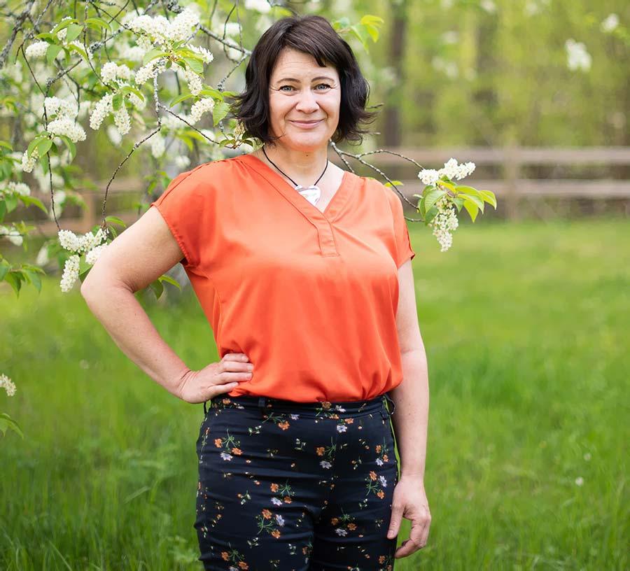 Susanne Sabith - Din Framstegscoach - står framför en häggbuske och utstrålar glädje och energi.