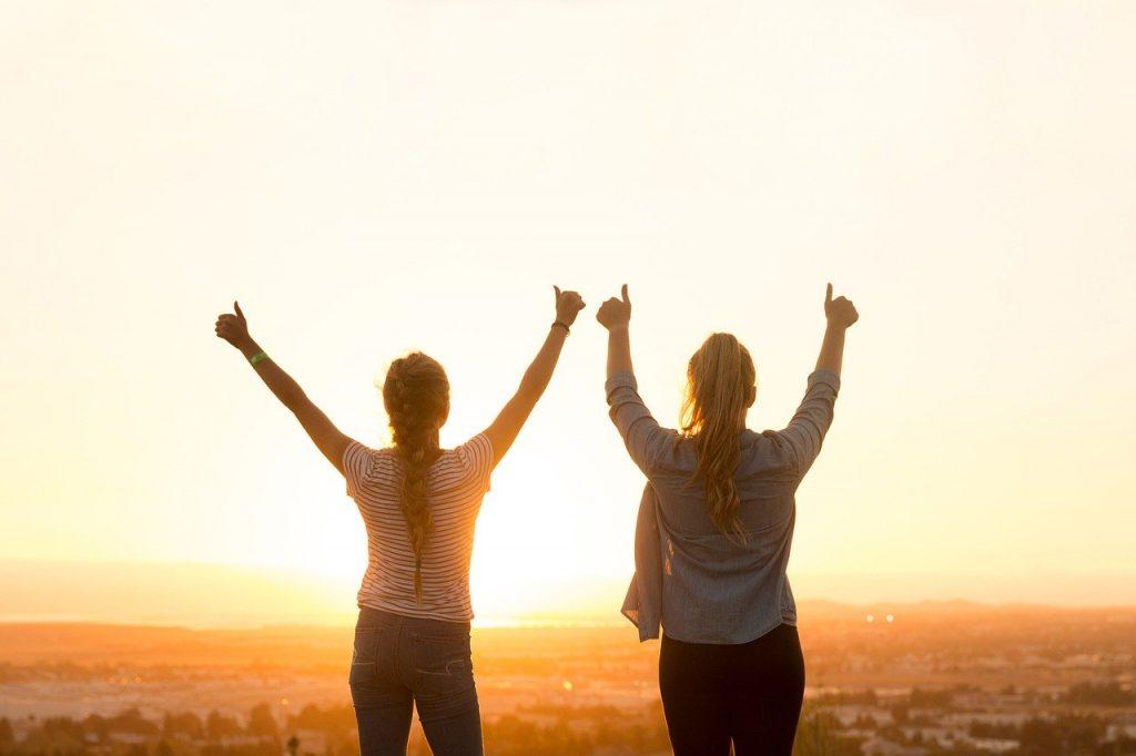 Två kvinnor som gör tummen upp mot sollnedgången. Du kommer också att göra tummen upp efter Susannes coachning och mentala träning.