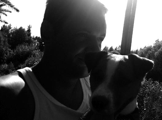 Bild: svartvitt fotografi med Robert Jonsson i vit undertröja tillsammans med hunden Wiggo.