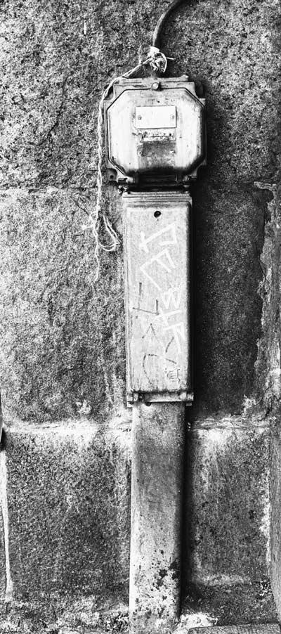 Bild: svartvitt foto på en stengrund till ett hus, eldosor med graffiti, en kabel och ett snöre bundet vid.