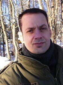 Bild: Robert Jonsson som skrivit diktsamlingen Bruksbilder, stående i ett vinterlandskap med öronlappar på sig