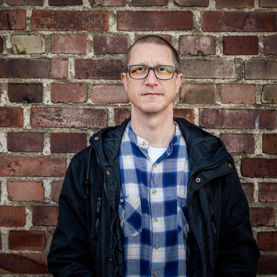 bild: Porträtt av Stefan Albrektsson, i fonden en tegelvägg