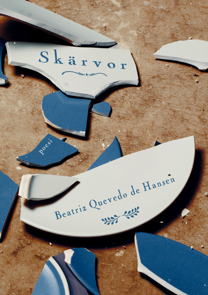 BILD: Omslaget till 'Skärvor' av Beatriz Quevedo de Hansen, på bilden en krossad tallrik i blått porslin på ett brunt golv
