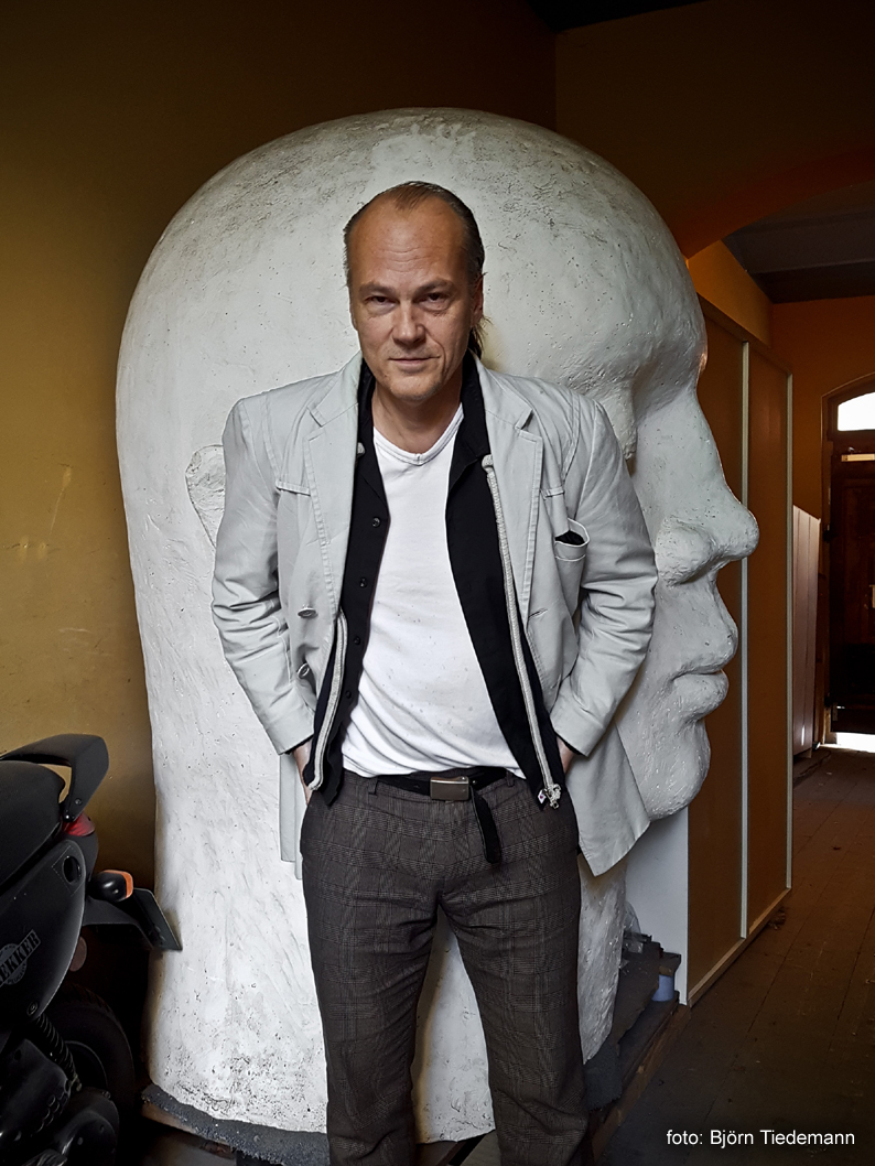 BILD: Håkan Sandell stående i ljus kavaj framför ett stort huvud, foto: Björn Tiedemann