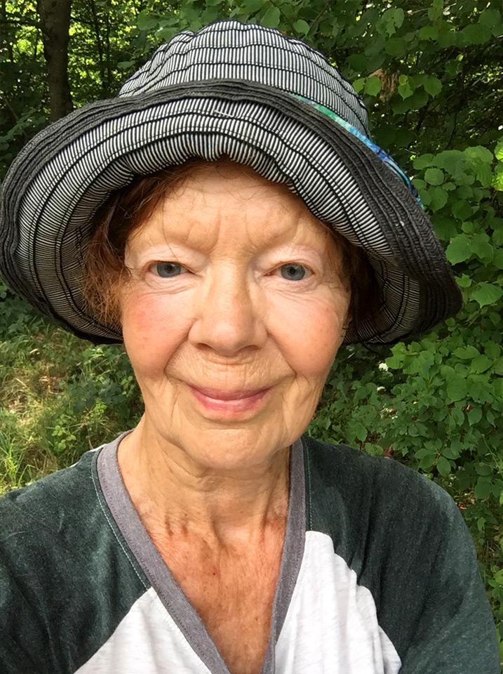 BILD: porträtt av Kerstin Park i friluftshatt framför sommargrönska