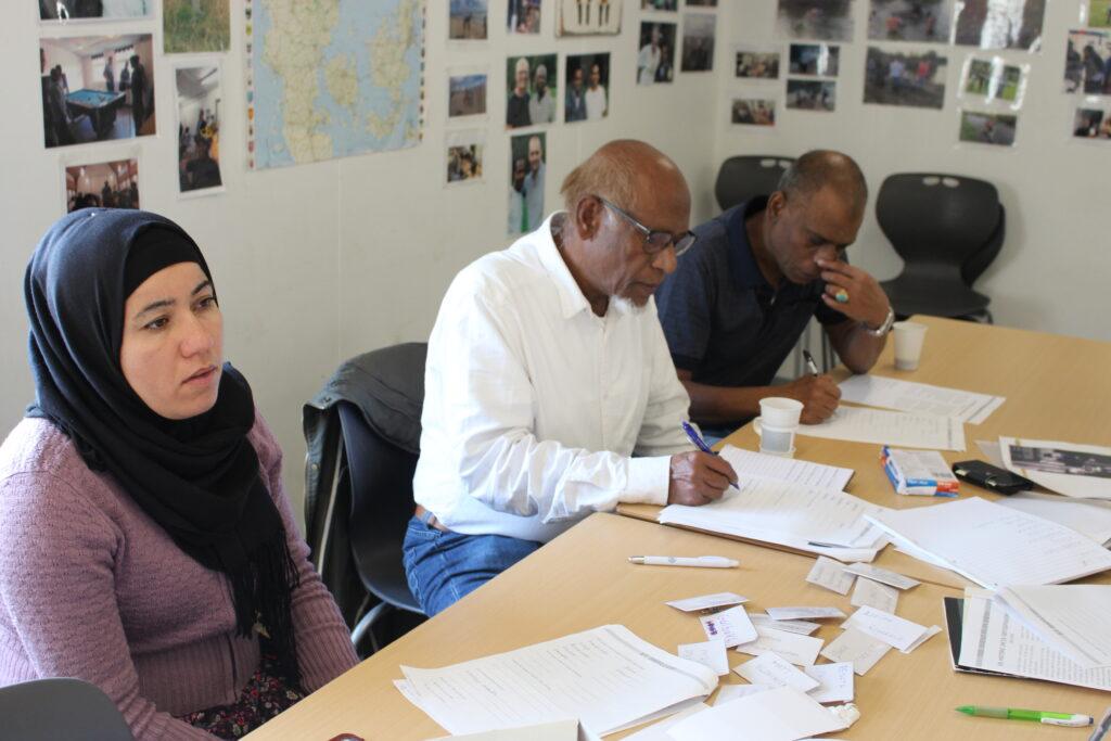 To mænd med brun hudfarve og en kvinde med lys hudfarve sidder omkring et bord, med papir foran sig. De sidder til sprogcafé og lærer dansk.