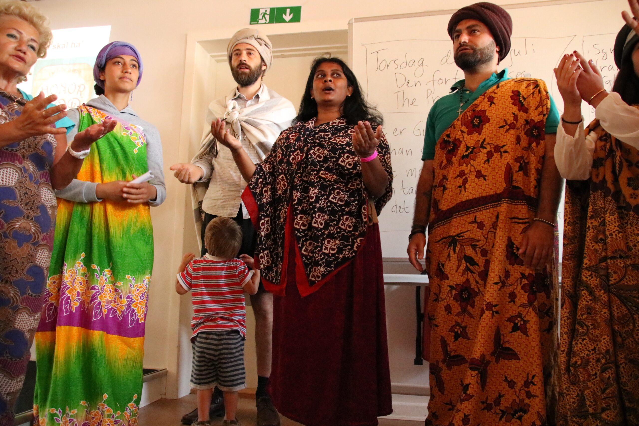4 kvinder, 2 mænd og et barn er at se på billedet. De voksne mænd og kvinder står iført noget traditionelt tøj fra Indien. Barnet ser op til hans far.