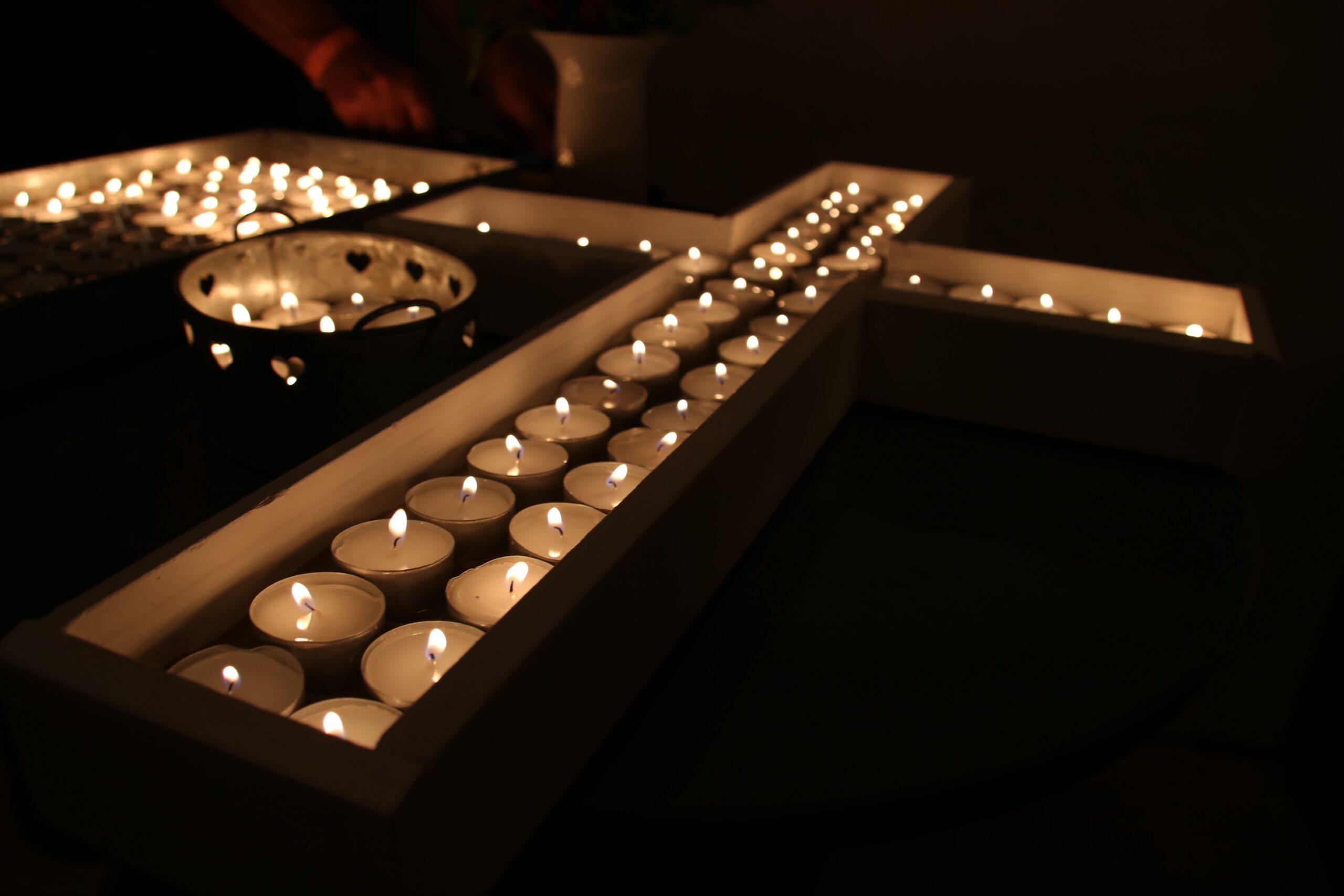 Billedet er dekorativt. Det viser et kors dannet af fyrfadslys.