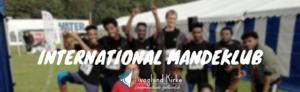 Billedet viser mandeklubben opstillet med løbetrøjer. Billedet er slørret og i fronten af billedet står International Mandeklub.