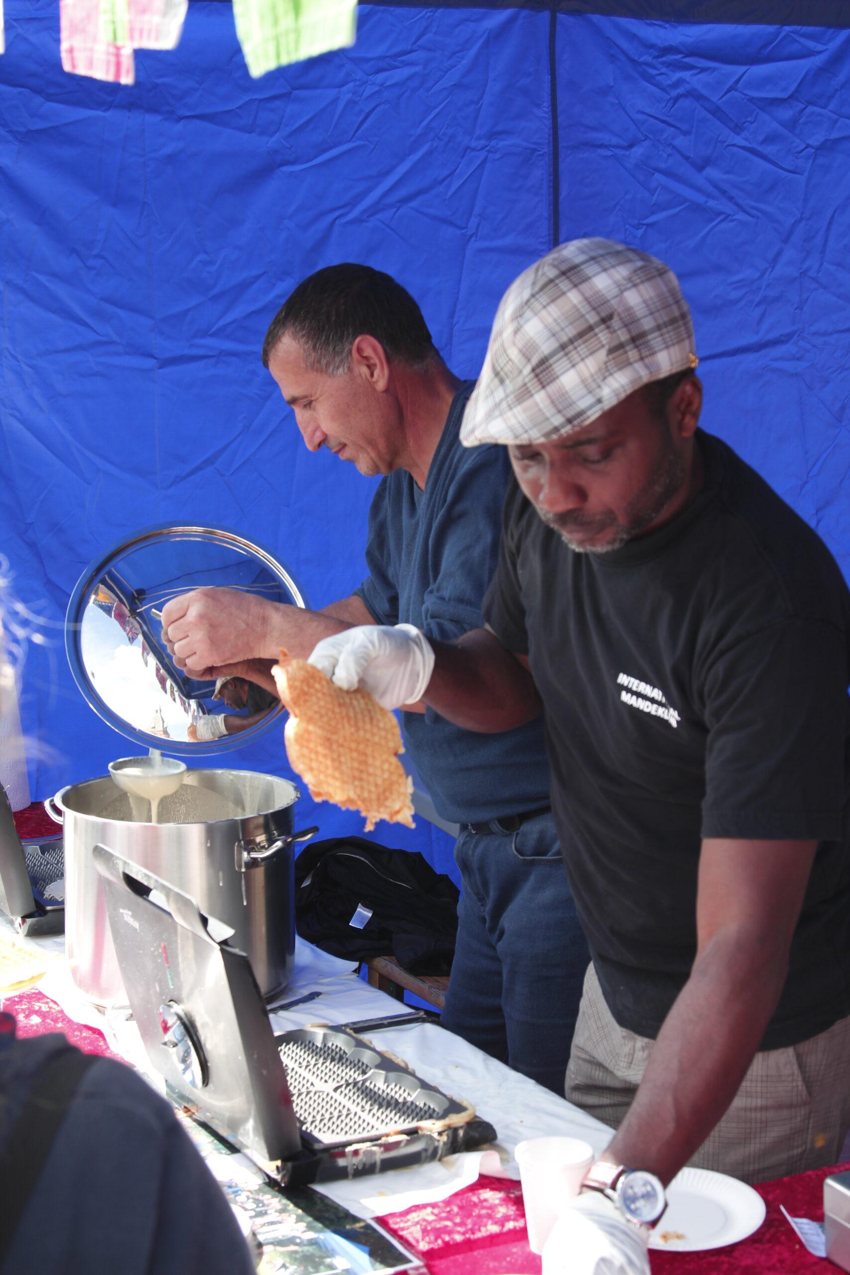 To mænd, én fra Kongo og en fra Iran står og laver vafler i en bod på International Day.