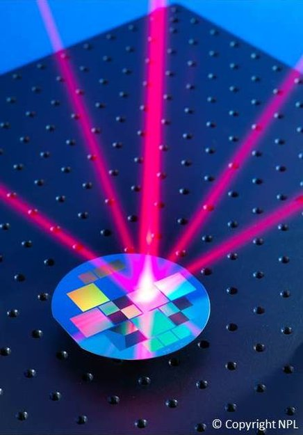 Laser beam shone on reflective wafer grating to trap atoms