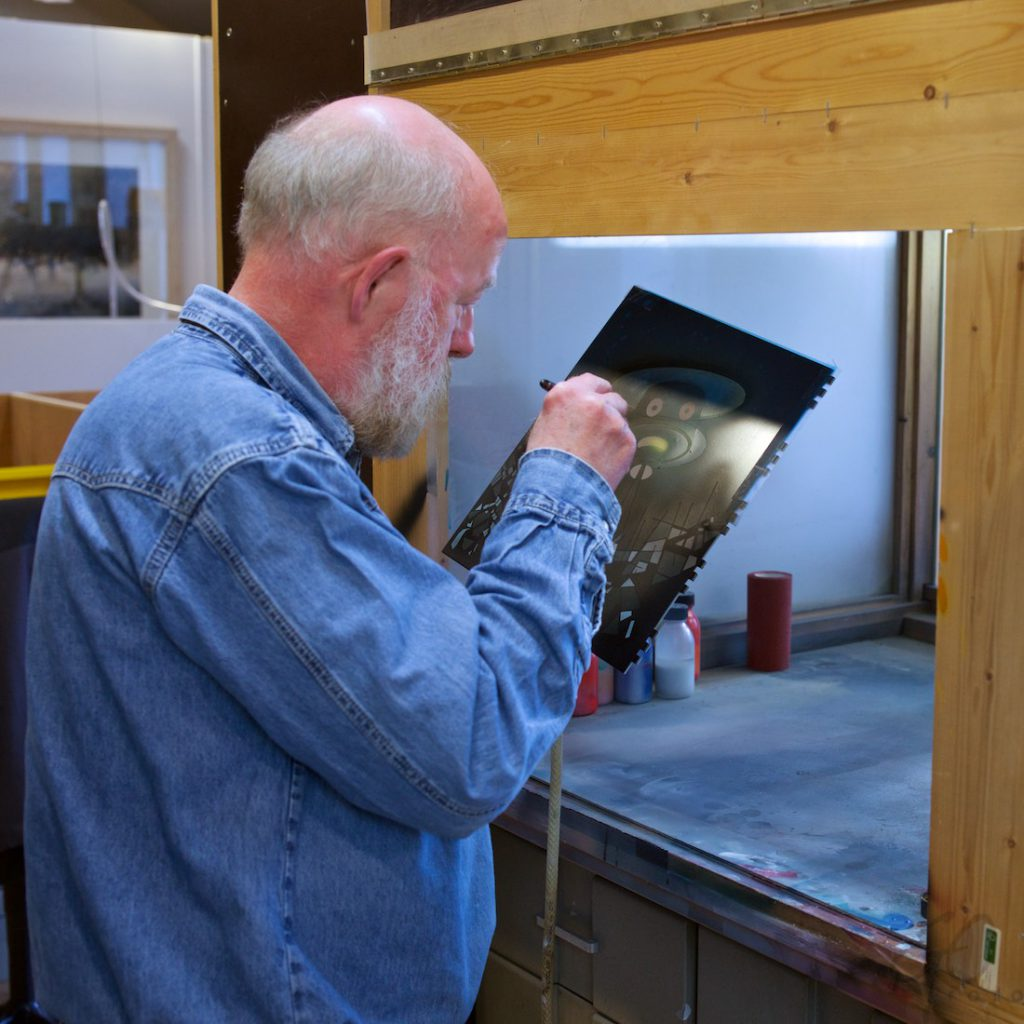 Beeldenstorm door een kloostertoer. Foto van een oude man met een airbrush spuit.