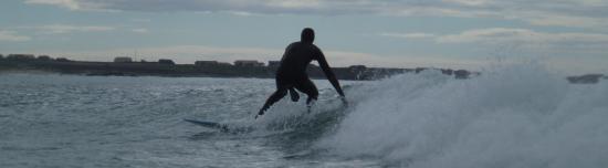 Ensom surfer i solnedgang