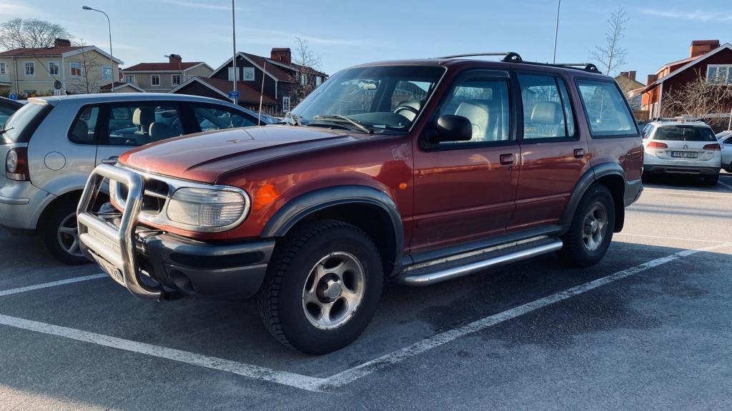 En röd Ford Explorer XLT från 1999 står parkerad i en parkeringsruta på en stor parkeringsplats.