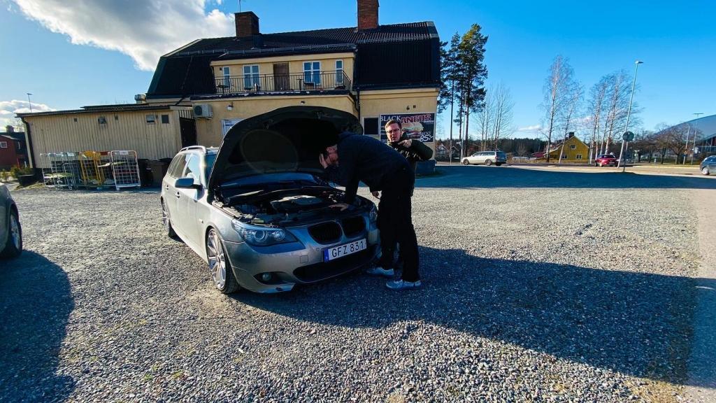 Hej Bruksbils presentatörer Magnus och Theo står och tittar ner under motorhuven på en BMW 525D E61. I bakgrunden syns Monroes i Sandviken.