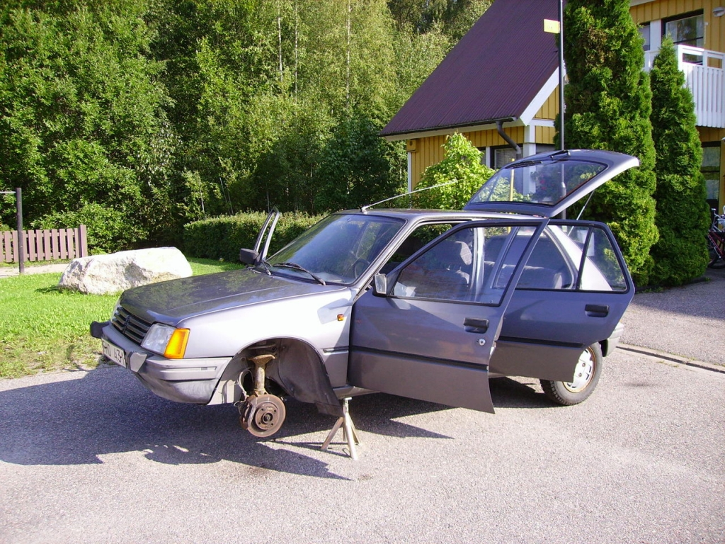 Hej Bruksbils presentatör Theo's första bil, en antracitgrå Peugeot 205 GR från 1985. Står på pallbockar framför ett gult hus.