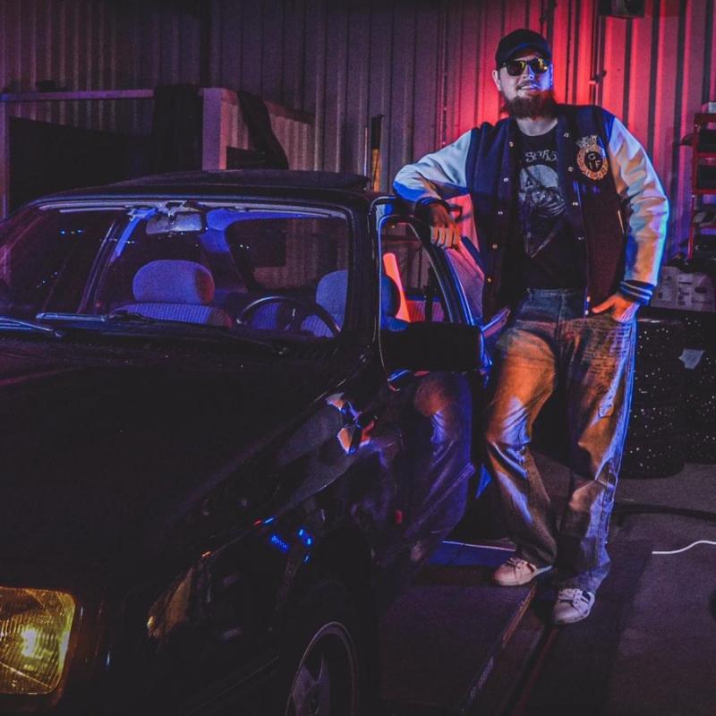 Hej Bruksbils presentatör Magnus står och poserar bredvid en Ford Sierra 2.0i Laser från 1985. Bilden har 80-talstema.