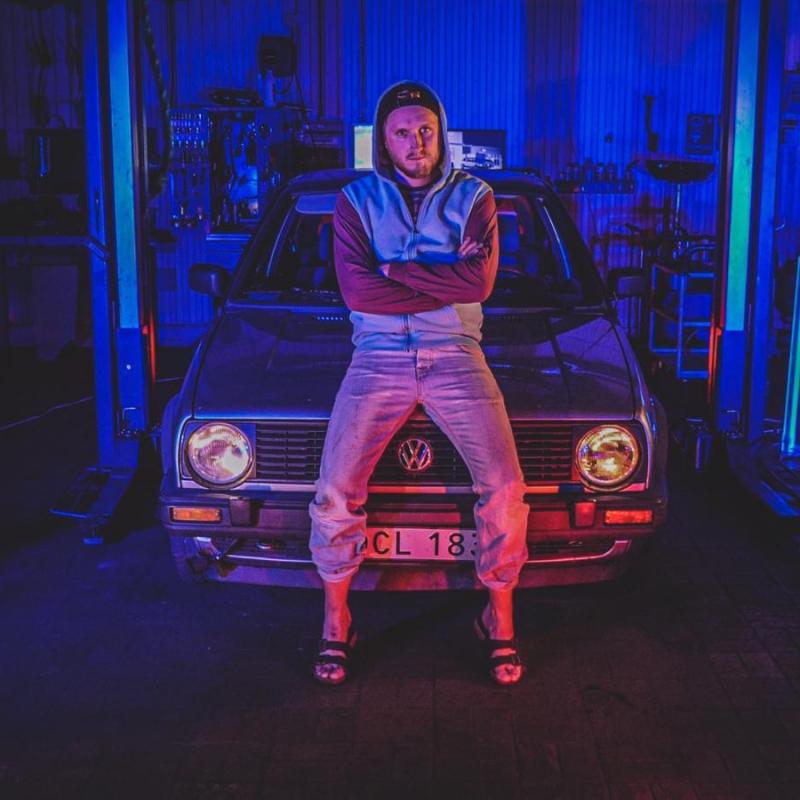Hej Bruksbils presentatör Nils står och poserar framför en Volkswagen Golf II från 1989. Bilden har 80-talstema.