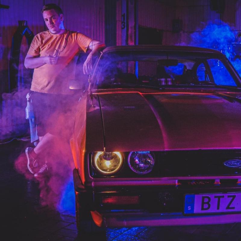 Hej Bruksbils presentatör Theo står och poserar bredvid en Ford Capri 2.0S från 1980. Bilden har 80-talstema.
