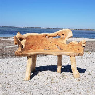 Träbänk som står på strand vid blå himmel
