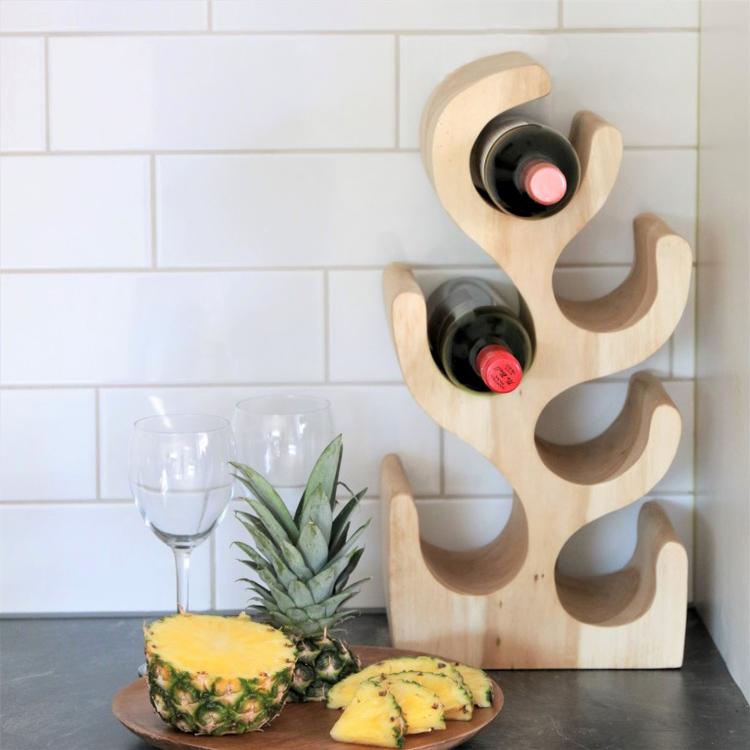 Vinställ på bänk med vinflaskor, vinglas och ananas