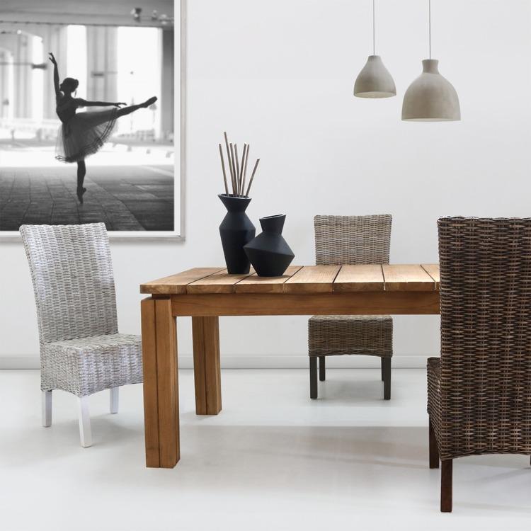 rustikt träbord med matstolar av rotting i olika färg