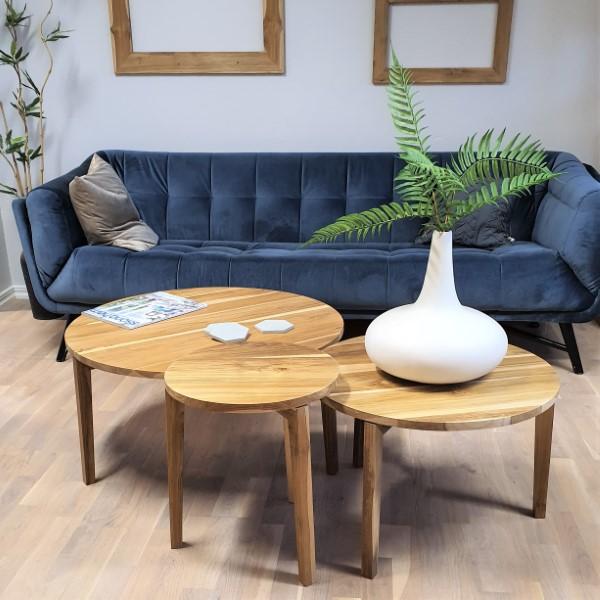 Tre runda bord av trä framför blå soffa