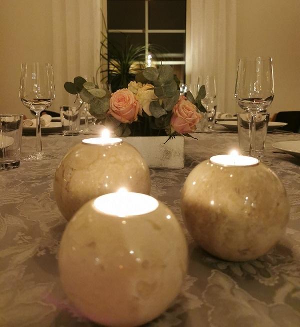 dukat bord med tända ljus i ljushållare av marmor