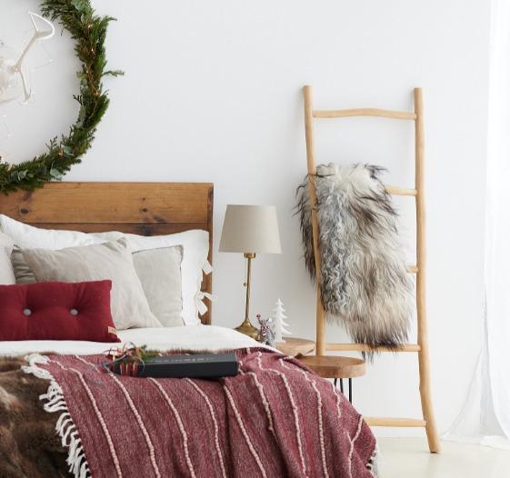 Säng med krans ovanför och dekorationsstege bredvid