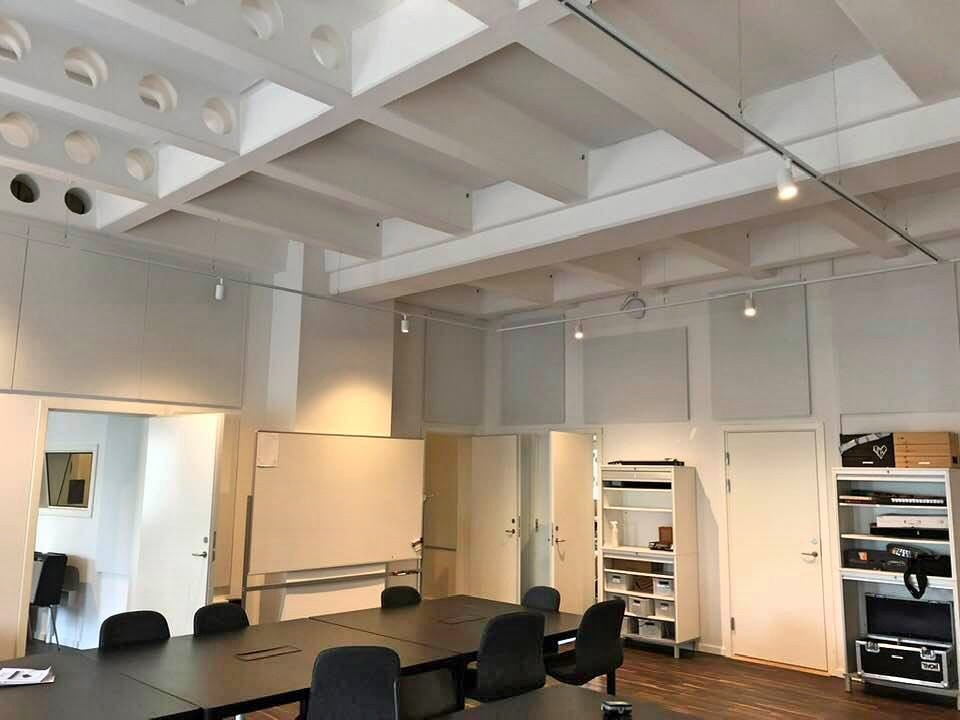 Room at the music and performance school 'Akademiet' in Copenhagen. White acoustic panels on the wall. All acoustics made by Intelligent Space (INSP)