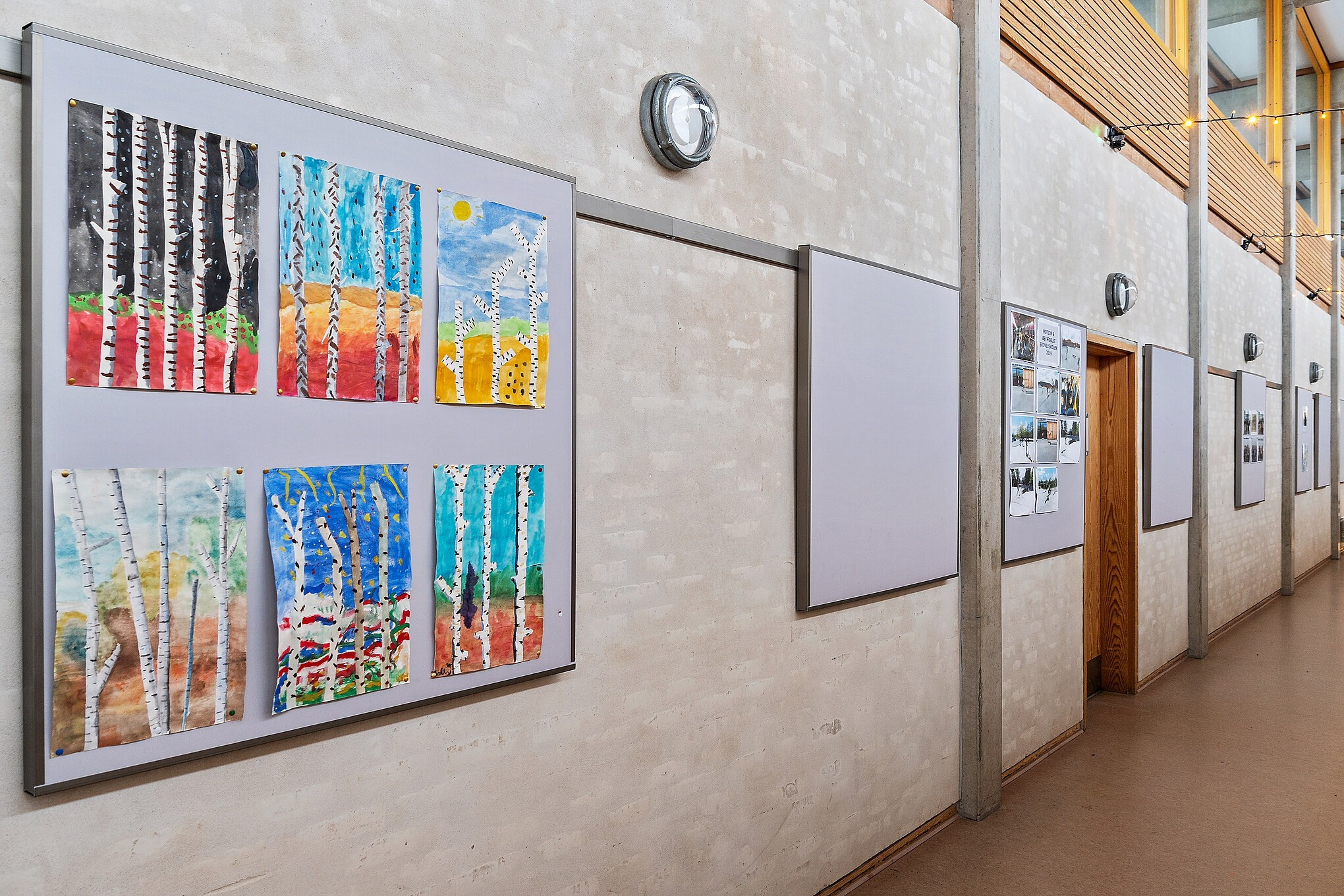 Hallway at Skovlyskolen with acoustic bulletin boards from Intelligent Space (INSP). Bulletin boards are framed in aluminium frames. On the boards, kids drawings are hanging.