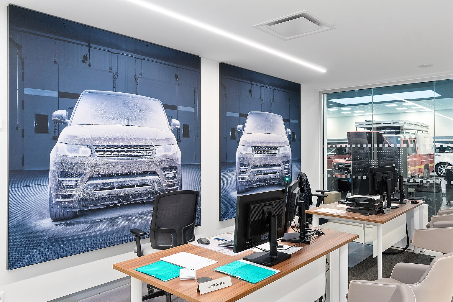 Acoustic pictures picturing Range Rover models hanging over desk tops at British MotorGroup in Søborg.