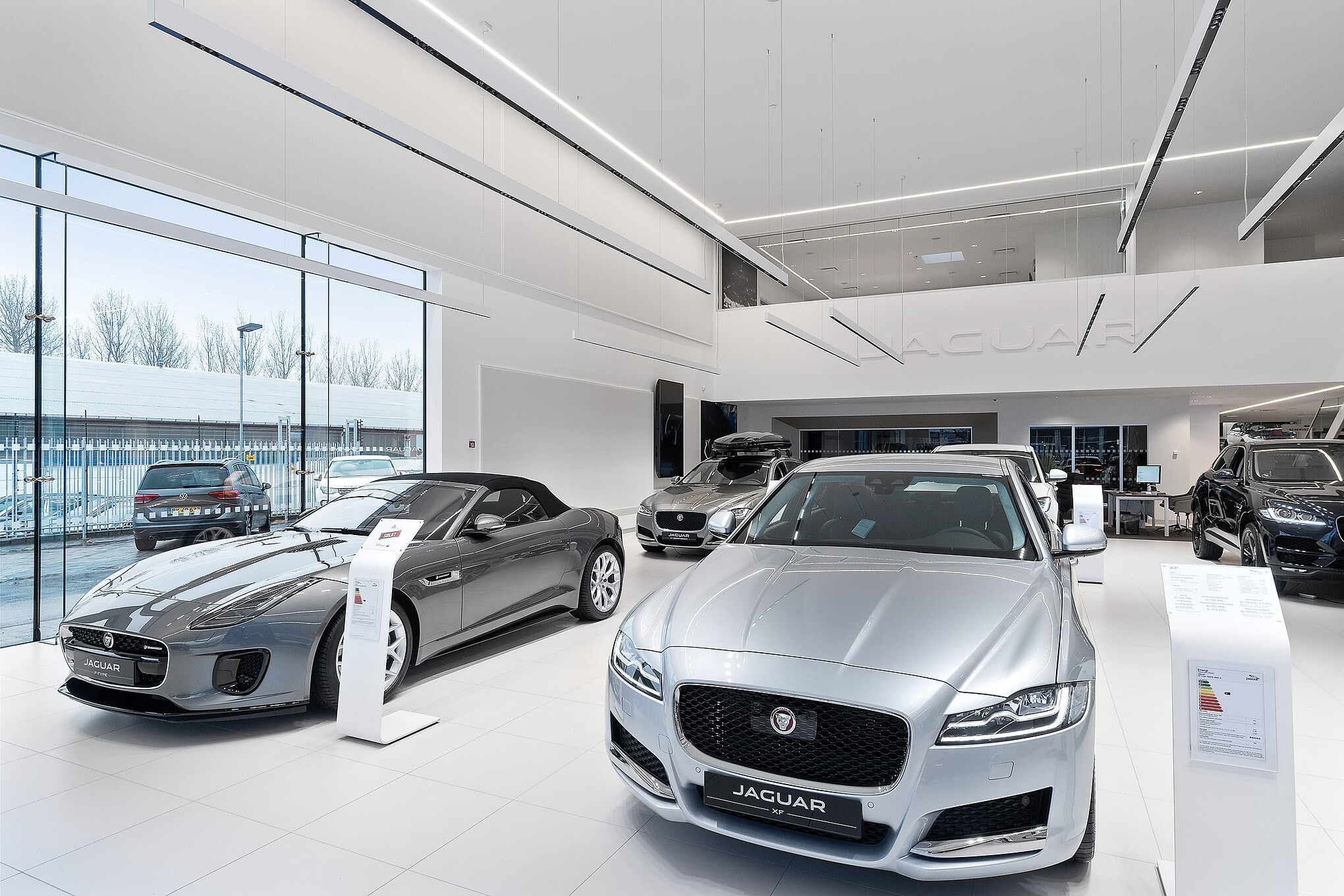 Jaguar showroom at British MotorGroup Søborg. On the walls white acoustic Soundscapes are mounted and slick jaguar cars fill out the room. All acoustic solutions made by Intelligent Space.