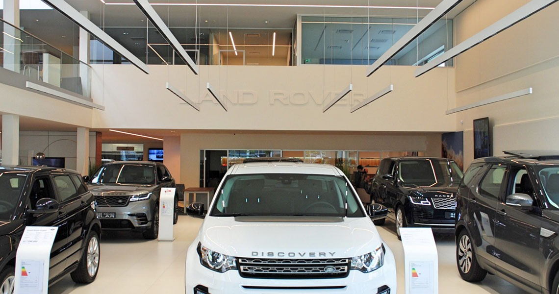 Showroom at British MotorGroup in Søborg, Denmark. Acoustic wall panels in frames on the walls and Land Rover cars. Made by Intelligent Space (INSP)