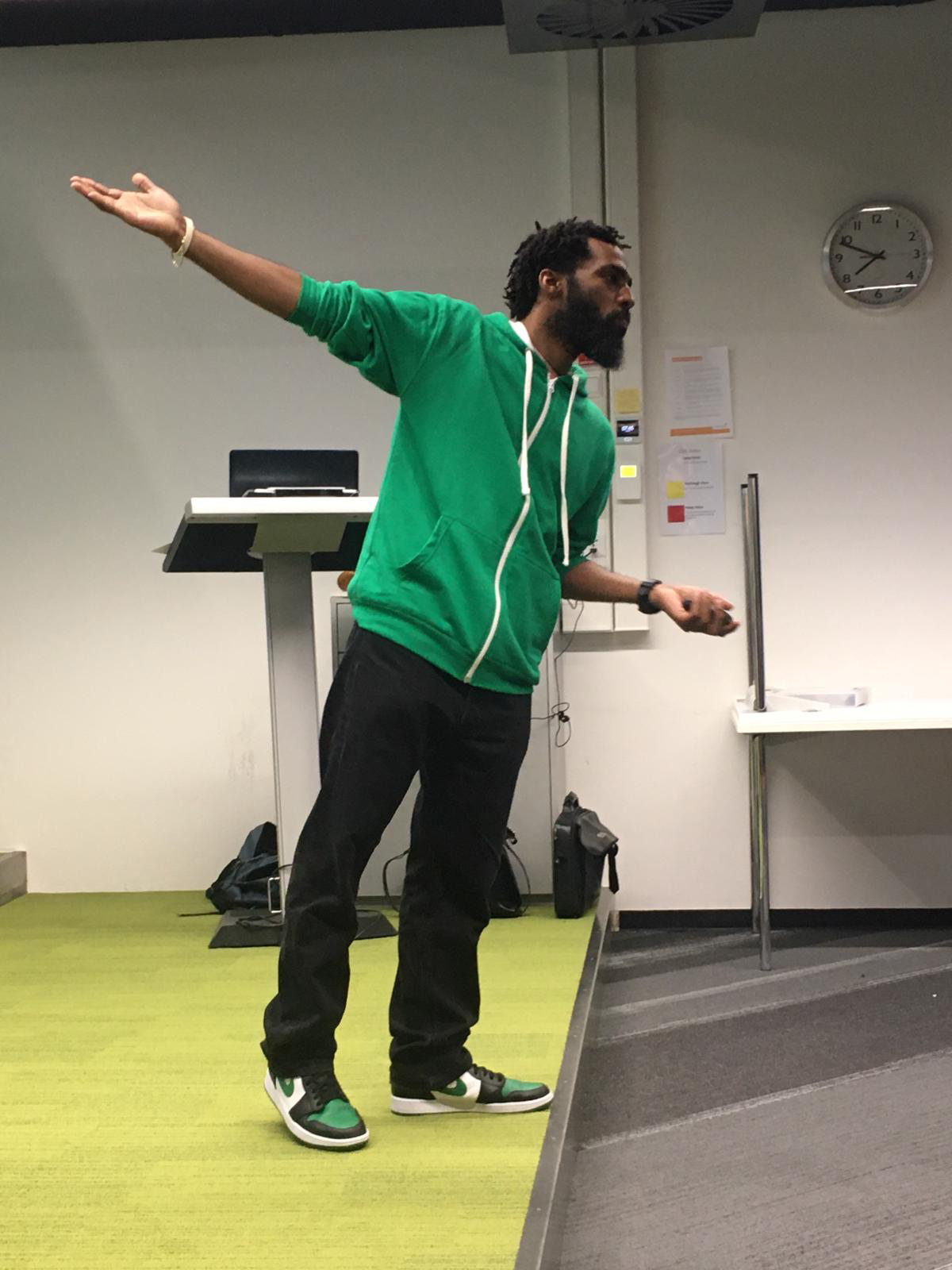 This is a photograph of the trainer and speaker Josuël Rogers pointing during a keynote speech