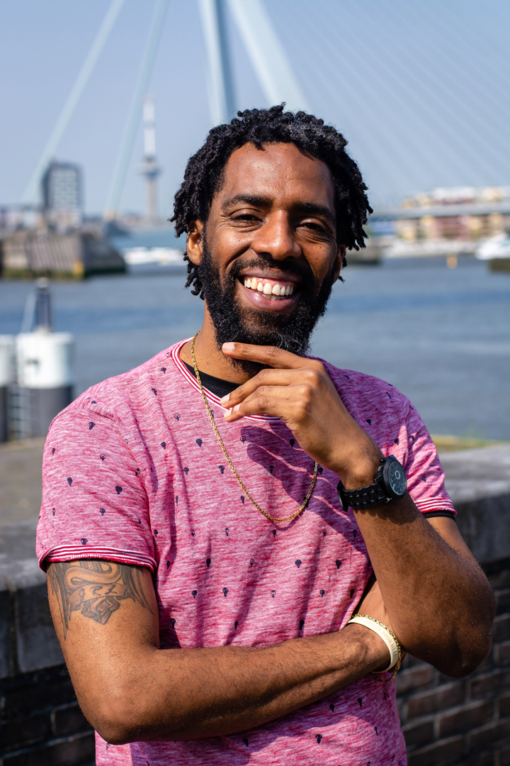 Dit is een foto van Josuël Rogers life coach die voor Erasmusbrug glimlacht