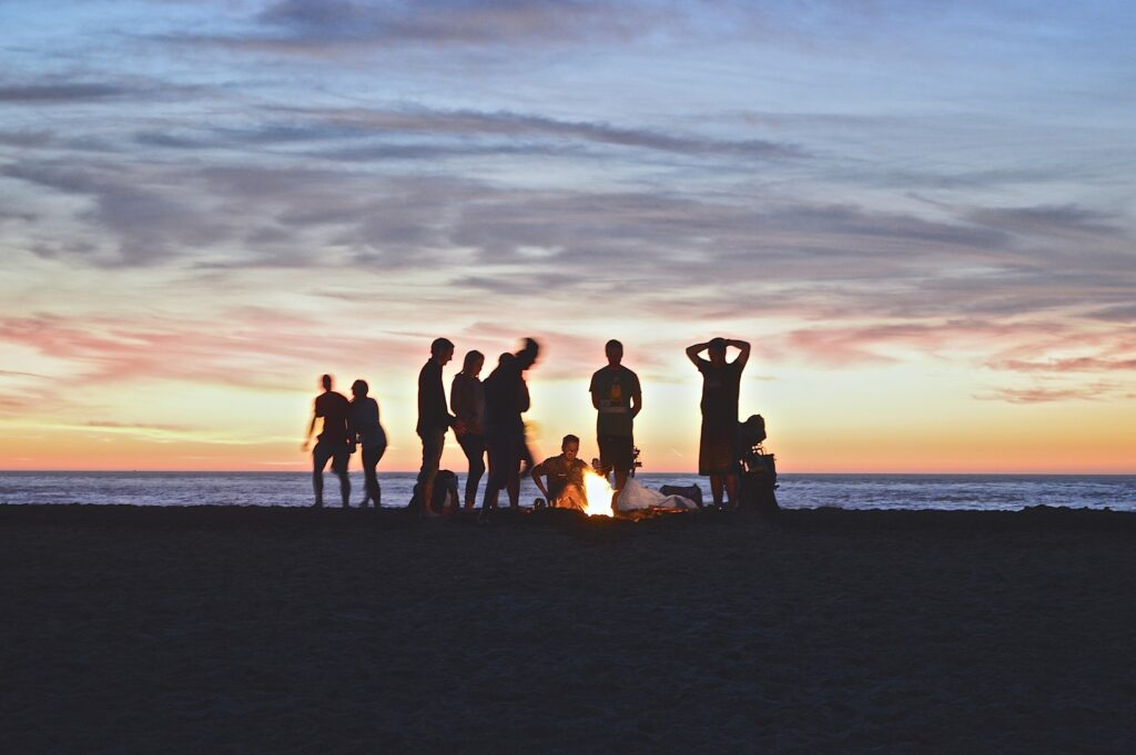 Small crowd at the beach with bonfire during sunset