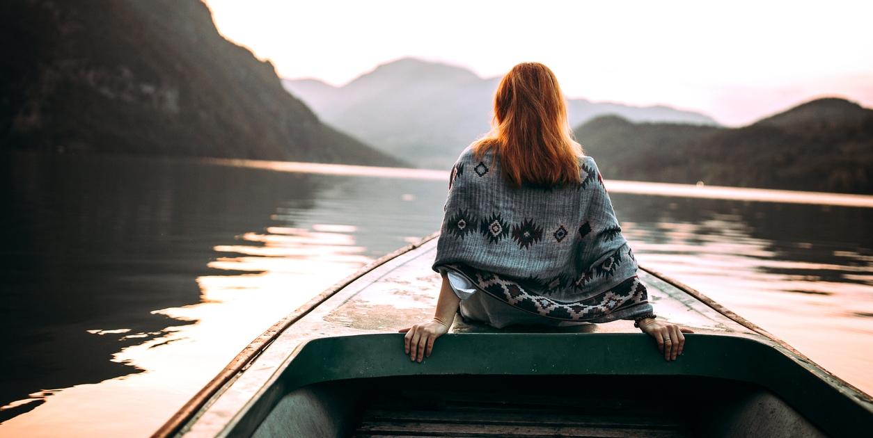 Bilde av ung dame i båt med ryggen til