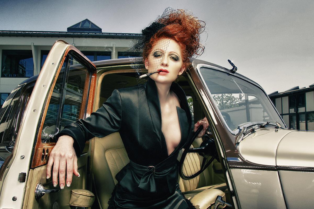 Kvinde med cigaret foran bil