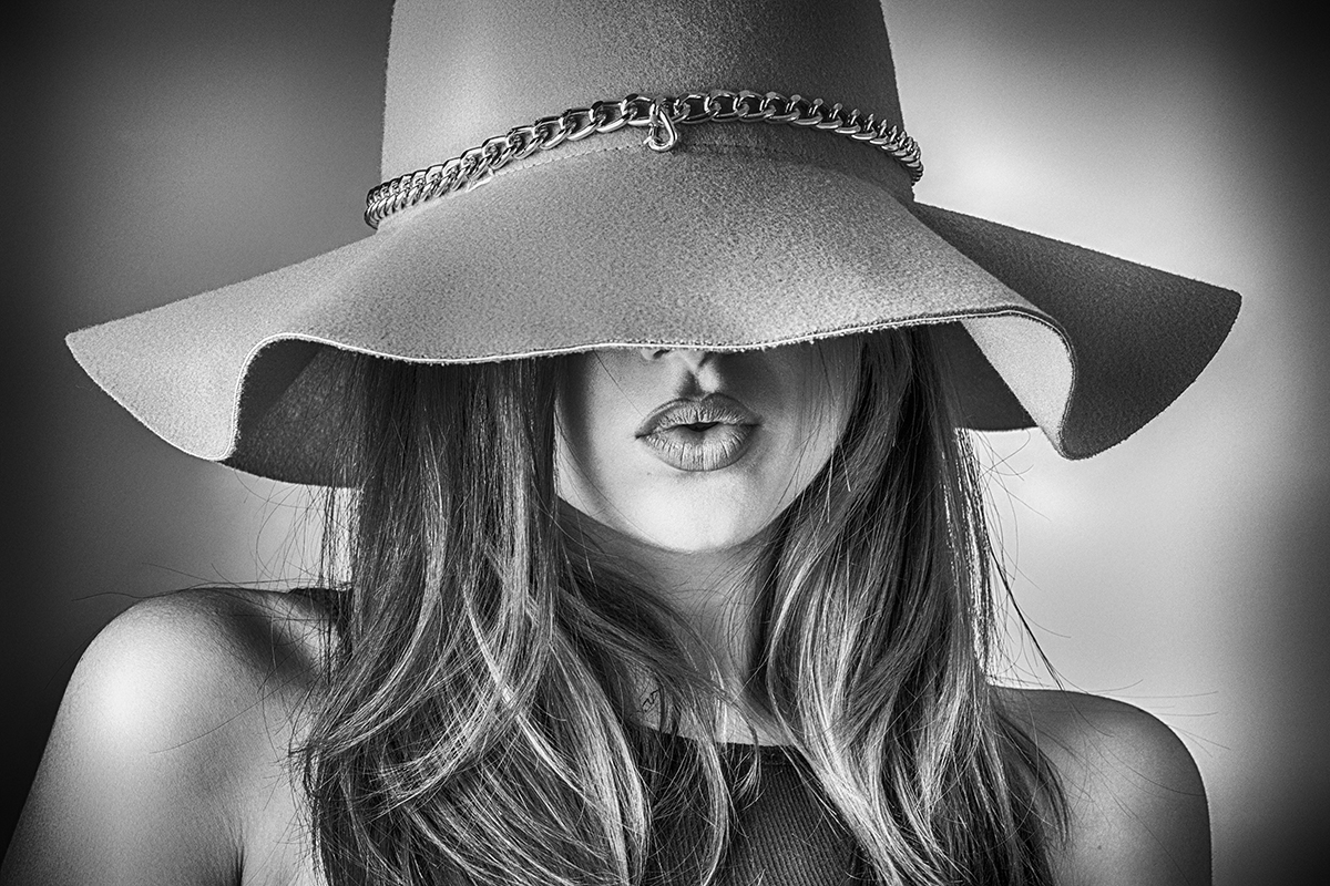 Kvindeansigt dækket af hat