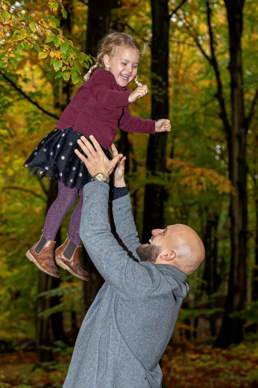 Far kaster datter op i luften ude i skoven