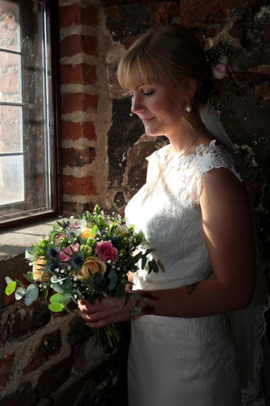 Hvid brud med blomsterbuket i hånden