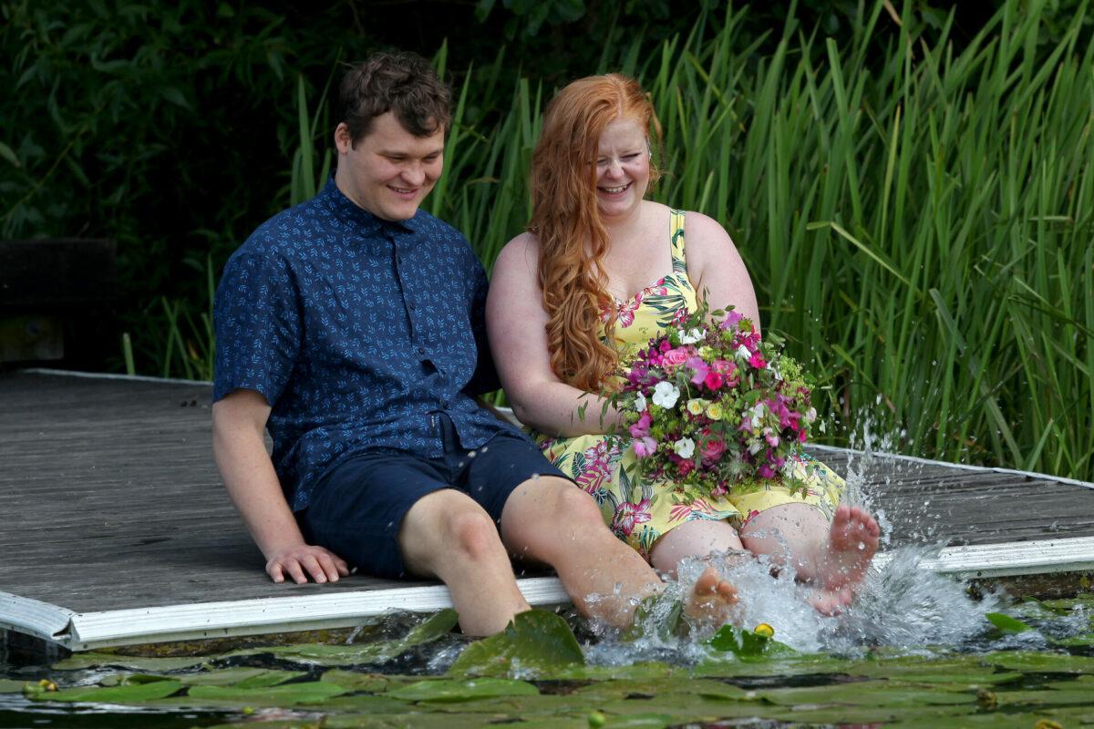 Kærestepar på træbro ud til sø med åkander
