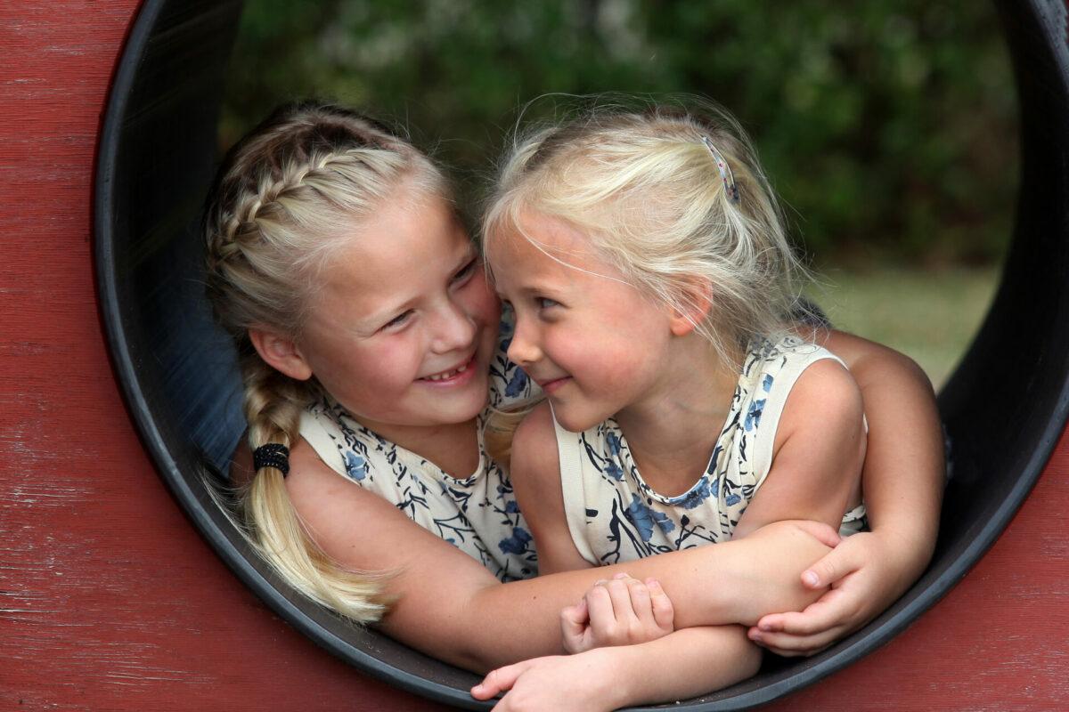 Portrætfoto af søstre på legeplads