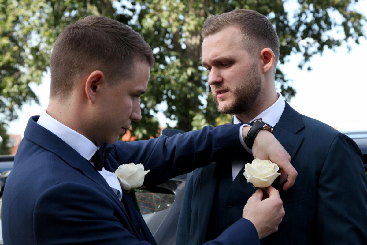 Bestman hjælper brudgom med blomsten