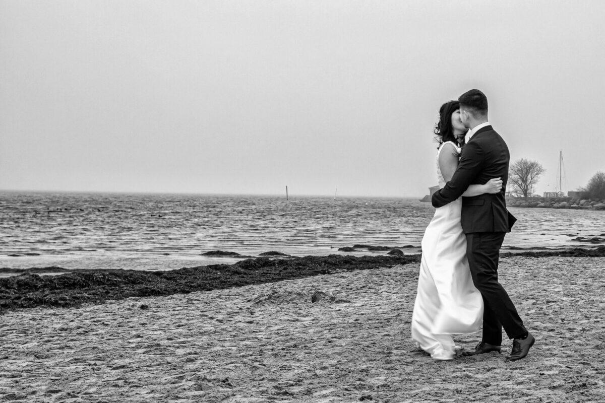 Brudepar kysser på strand