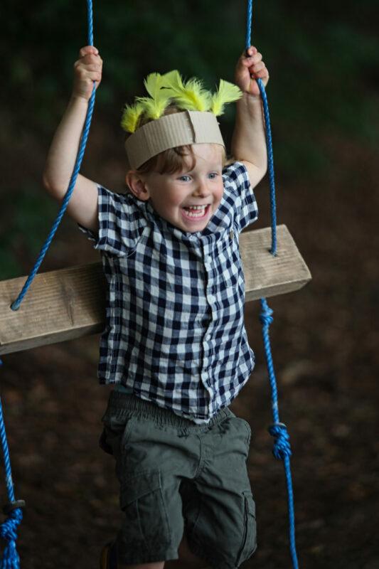 Dreng på en gynge ude i naturen