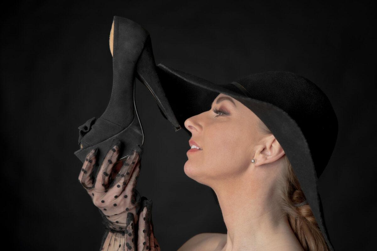 Kvinde holder en sort højhælet sko
