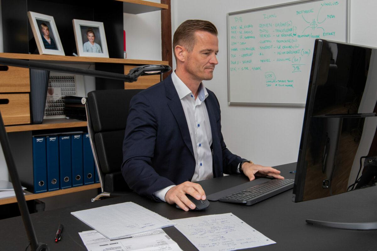 Mand arbejder ved computer på kontor